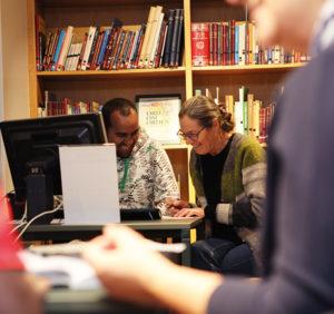 Läxhjälp Sadek Mohamed får hjälp av Kerstin Kolback med att hitta artiklar på nätet om bostadsmarknaden och jämföra innehållet. FOTO: Fredrik Svedemyr
